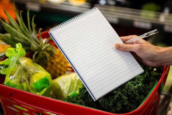 pessoa-segurando-lista-compras-a-frente-de-cestinha-com-frutas-legumes