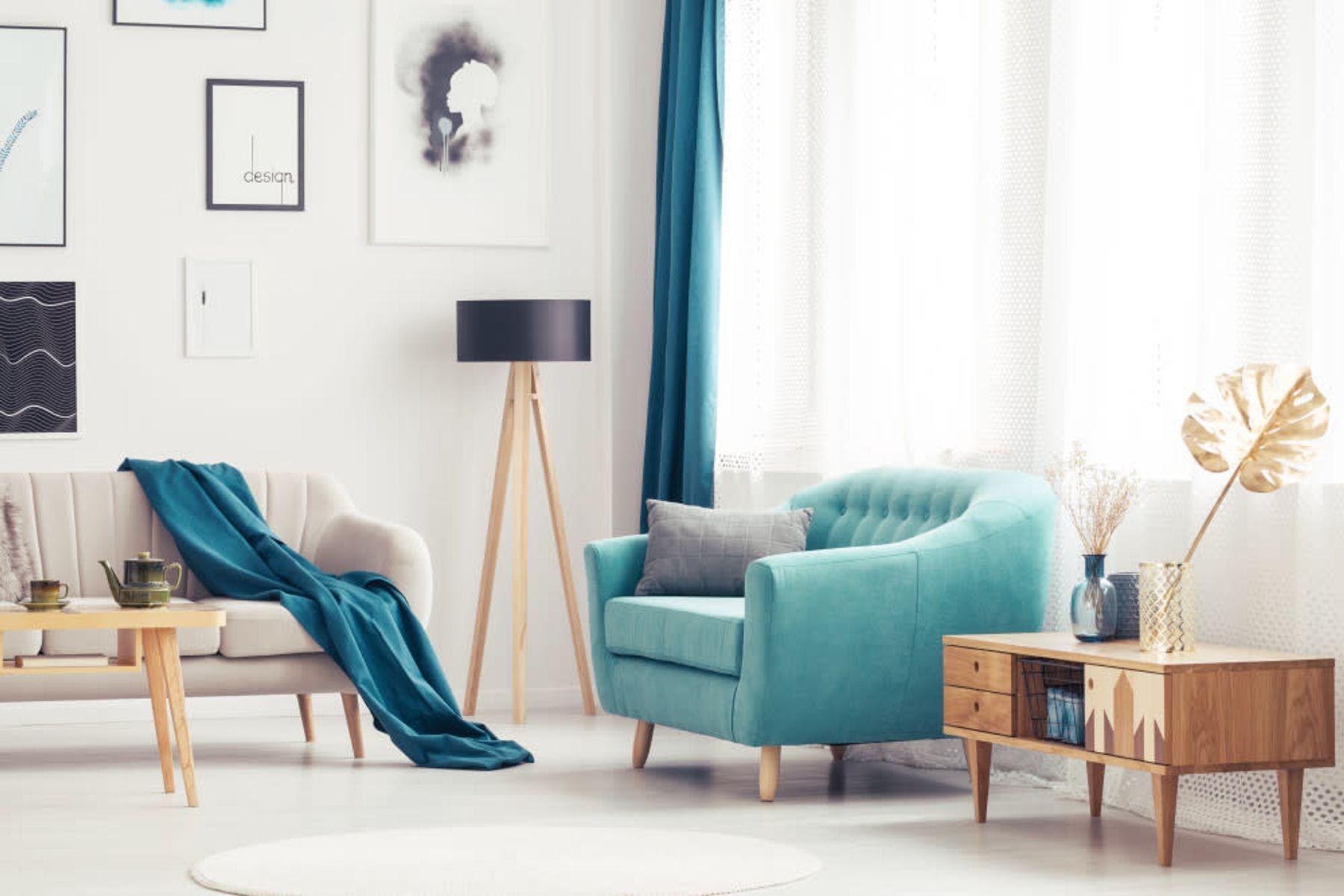 Aydınlık ve şık bir oturma odasında pencere önünde turkuaz berjer ve bej bir kanepe