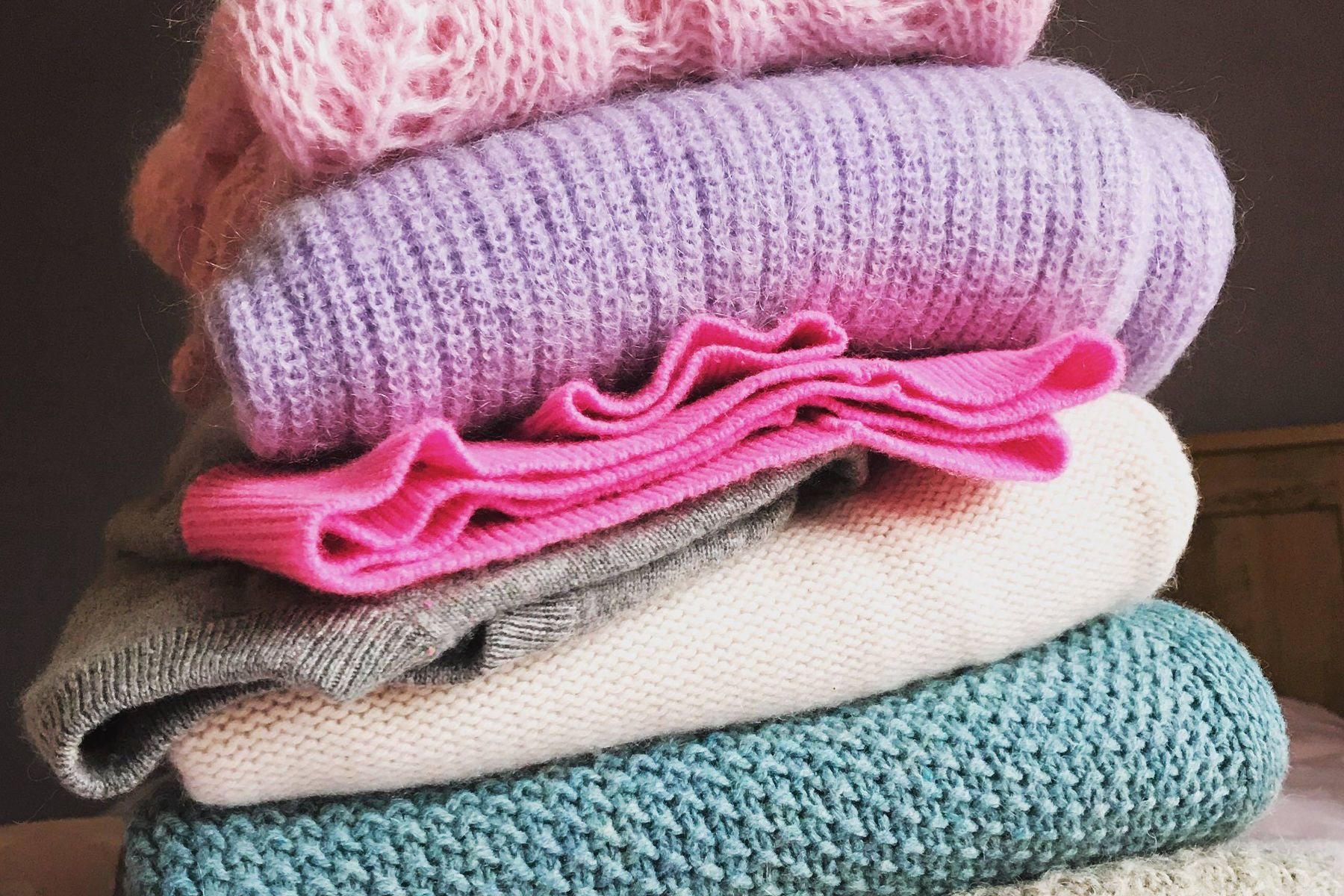 woolen clothes in pastel colors folded and stacked