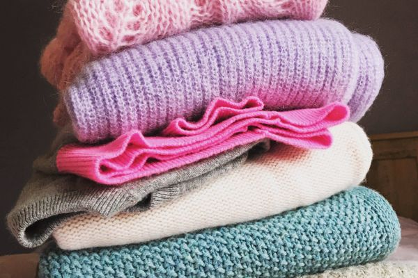 Haufen Wollpullover in Rosatönen