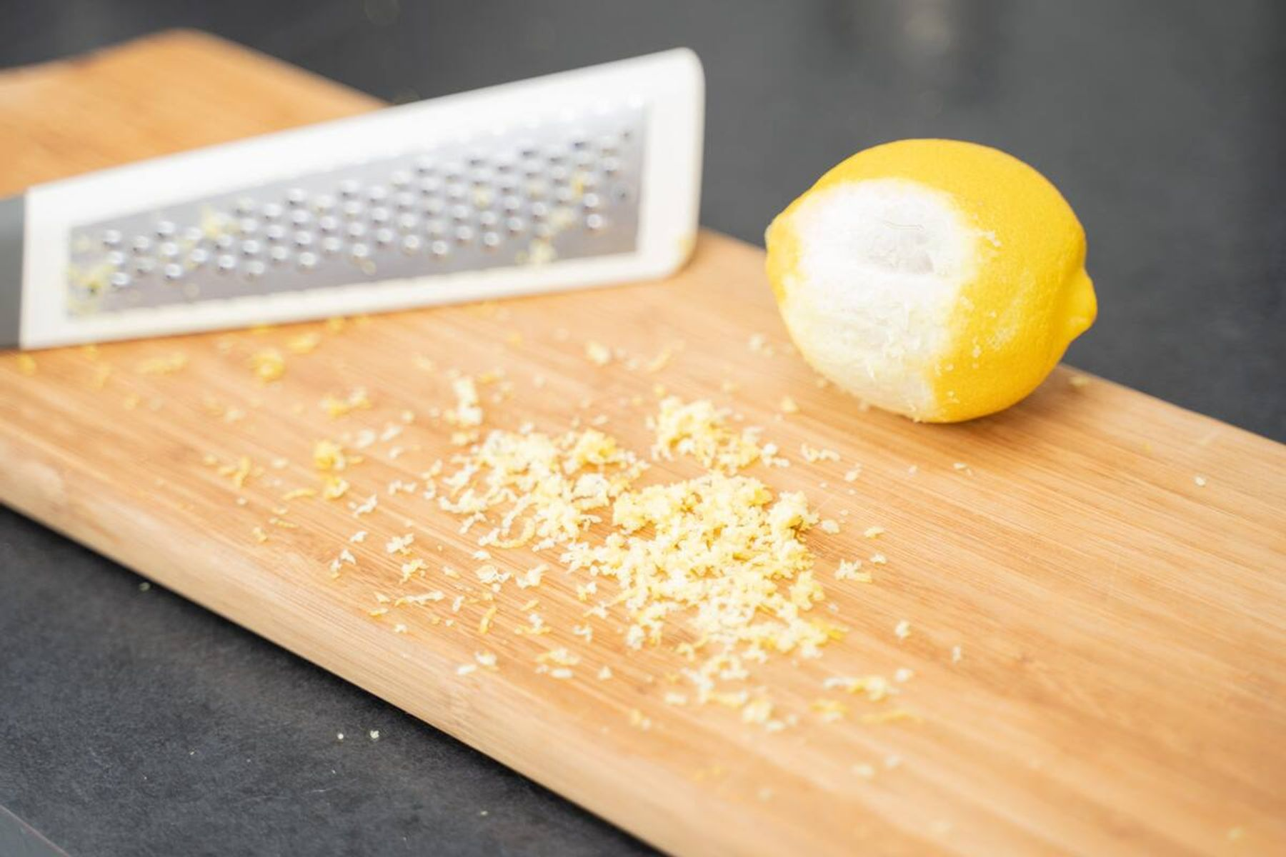 Grated lemon and grater on a chopping board