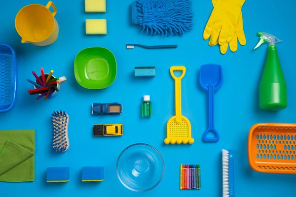 A collection of household cleaning equipment and  children's toys against a blue background