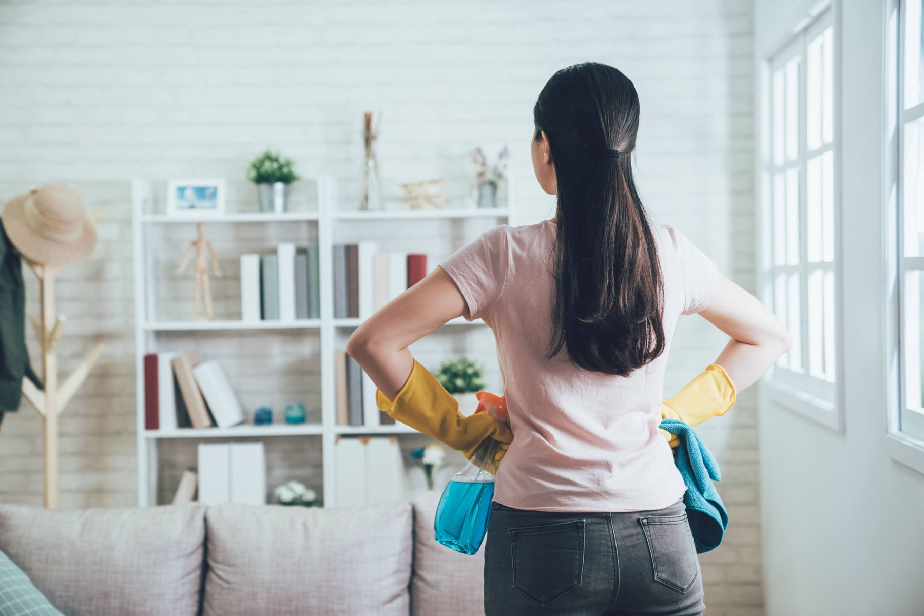 Mulher segurando borrifador olhando para a sala com sofá e estante com livros