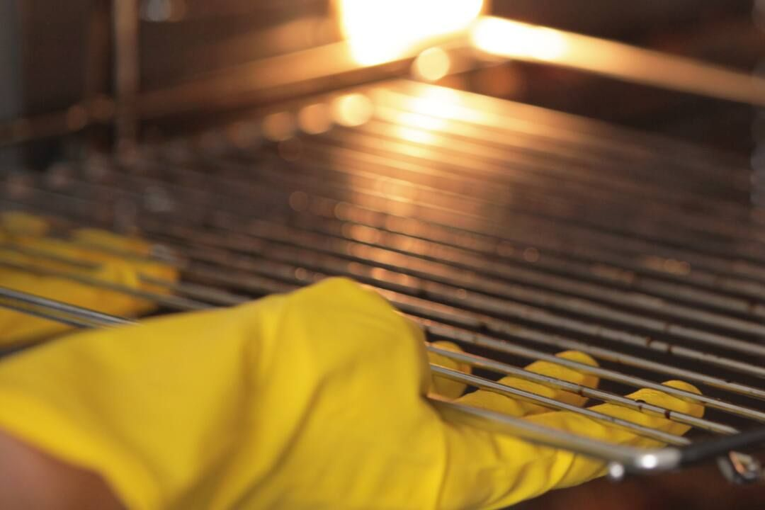 les mains dans des gants jaunes nettoyant le four