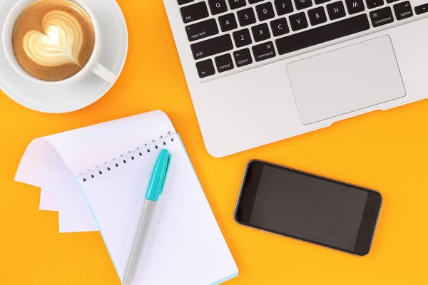 notebook, mobil, zápisník, pero a šálek kávy na oranžový stůl