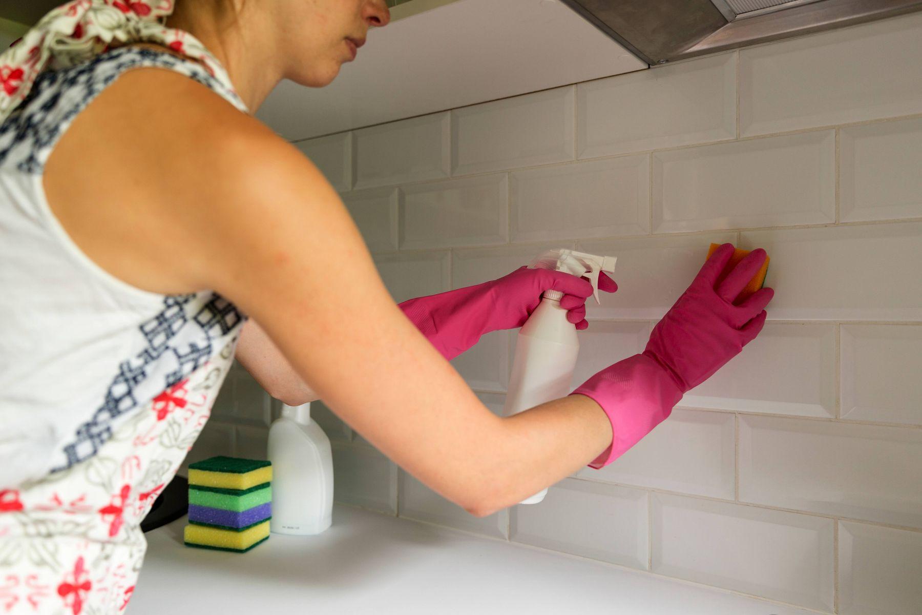 Pessoa com luvas rosas limpando o azuleijo da cozinha com multiuso e esponja