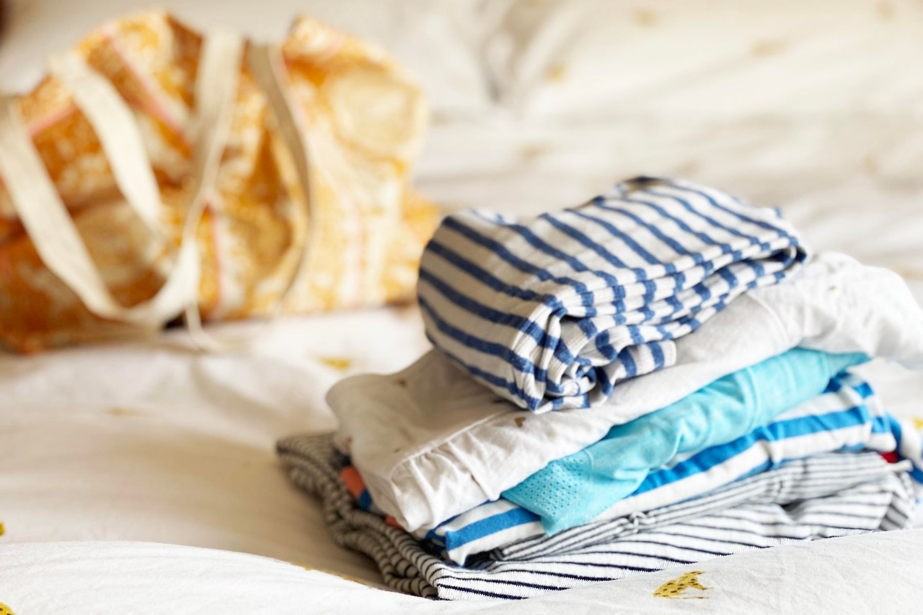 Assorted clothing folded on a bed, large fabric bag in the background