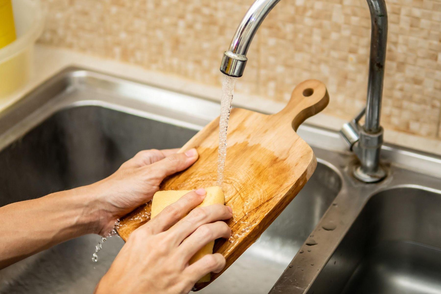 Homem lavando tábua de corte de madeira com água e esponja