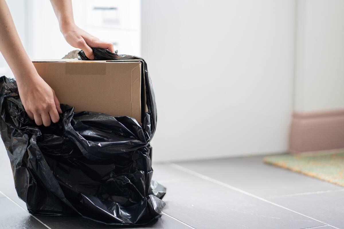 Cardboard box being put into a black plastic bag