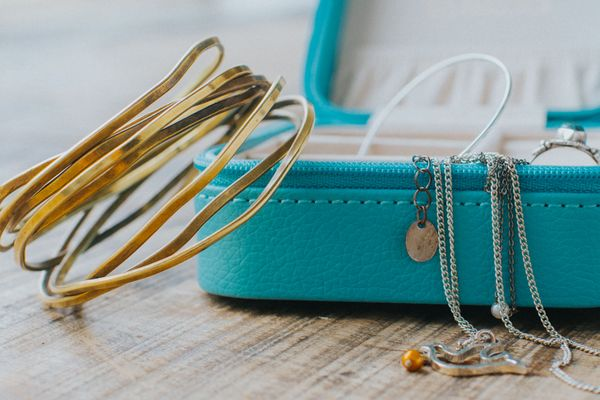 how to clean gold: gold bangles and gold and silver necklaces hanging from teal jewellery box