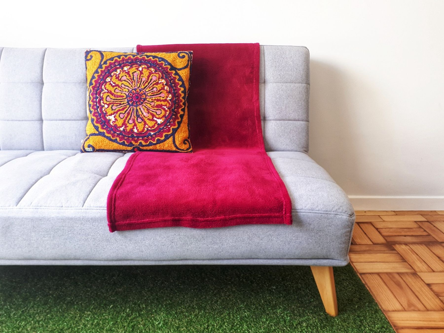 Sofa with a throw blanket and cushions.