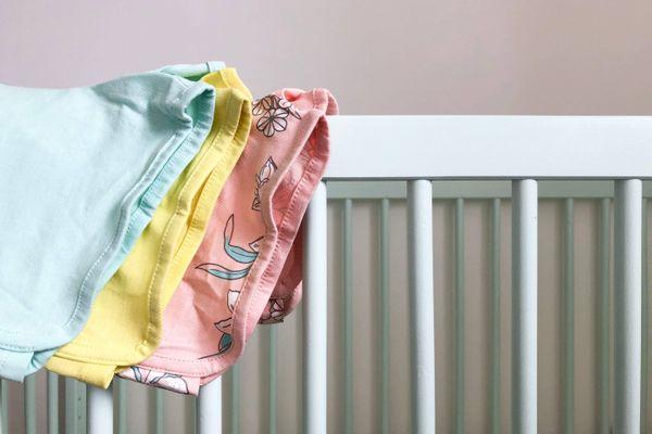 baby tøj hængende på krybbe gitter