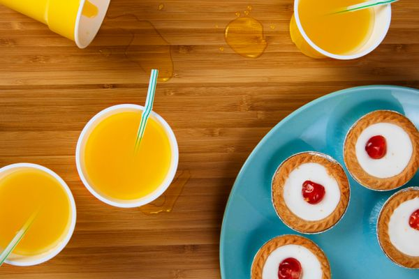 orange drinks and little tarts on a wooden table