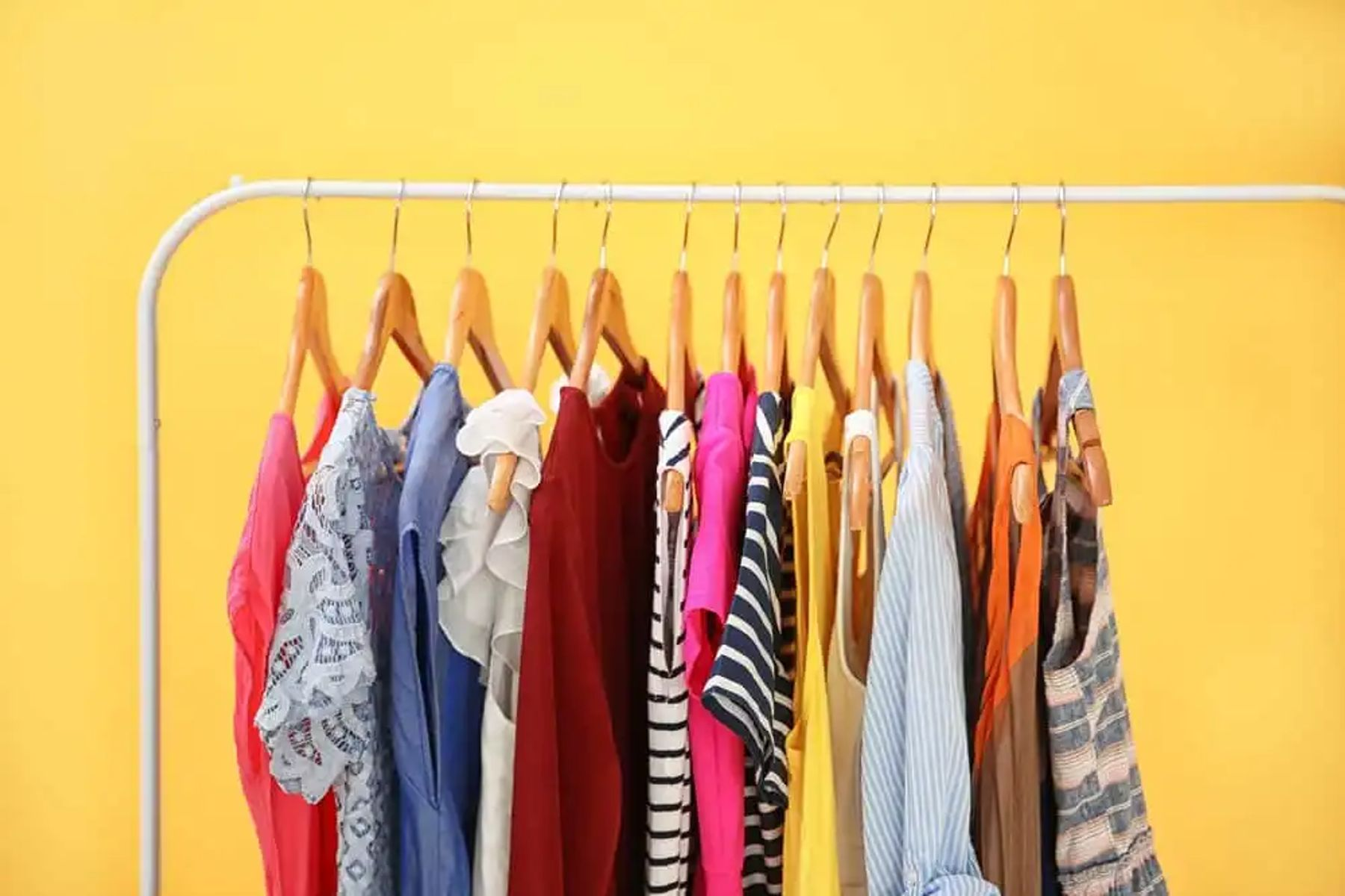 A rack of women's tops hanging from wooden hangers in front of a yellow background