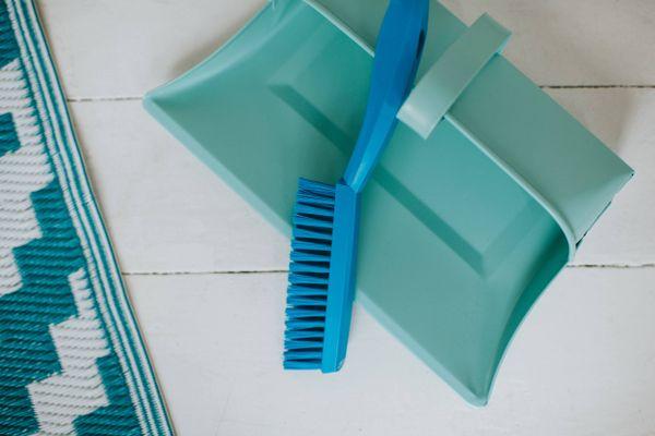 paletta blu e spazzola di pulizia sul pavimento di legno bianco