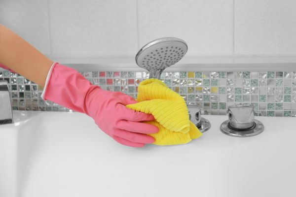 a hand in a pink rubber glove cleaning a silver tap with yellow cloth