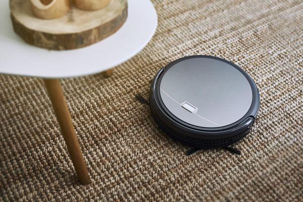 Robô aspirador limpa tapete ao lado de uma mesinha