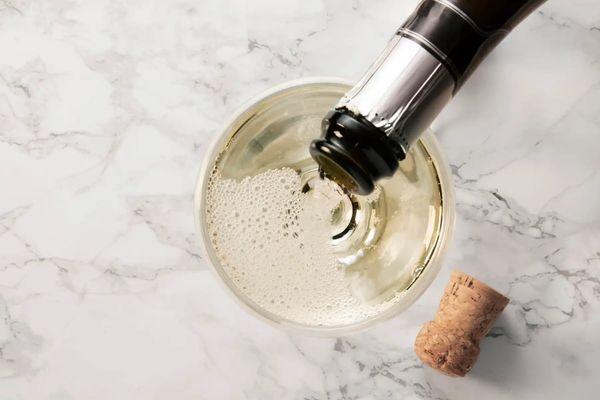 Botella de espumante llenando vaso y corcho