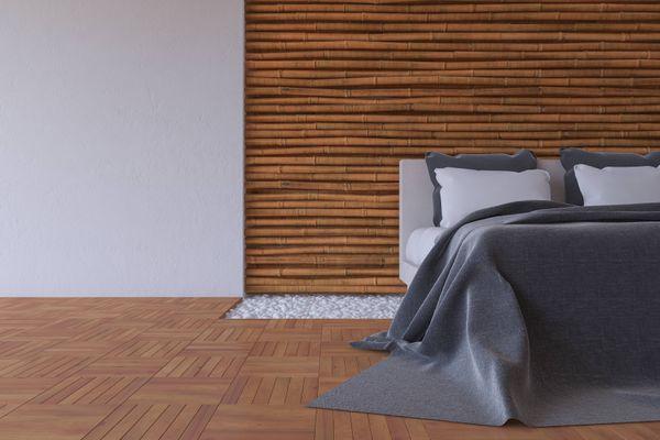 Quarto com piso laminado, cama arrumada e cabeceira de madeira