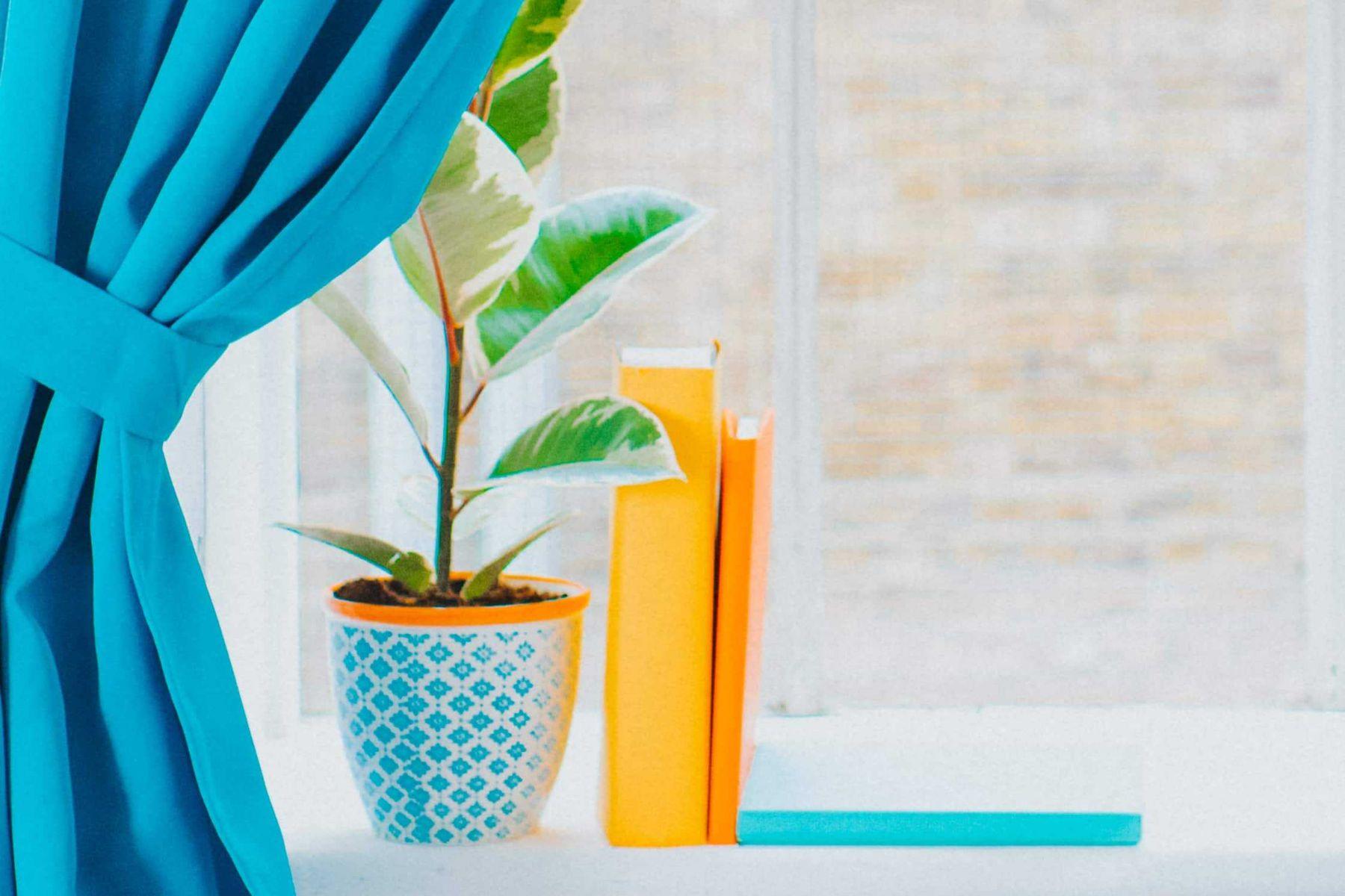 cortina-azul-cobrindo-parcialmente-janela-com-vaso-e-livros