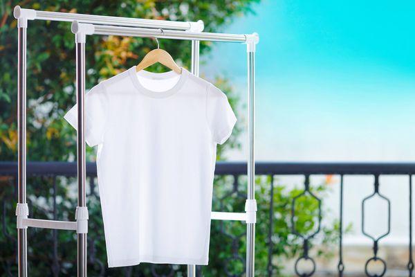 Camiseta branca pendurada na arara na área externa