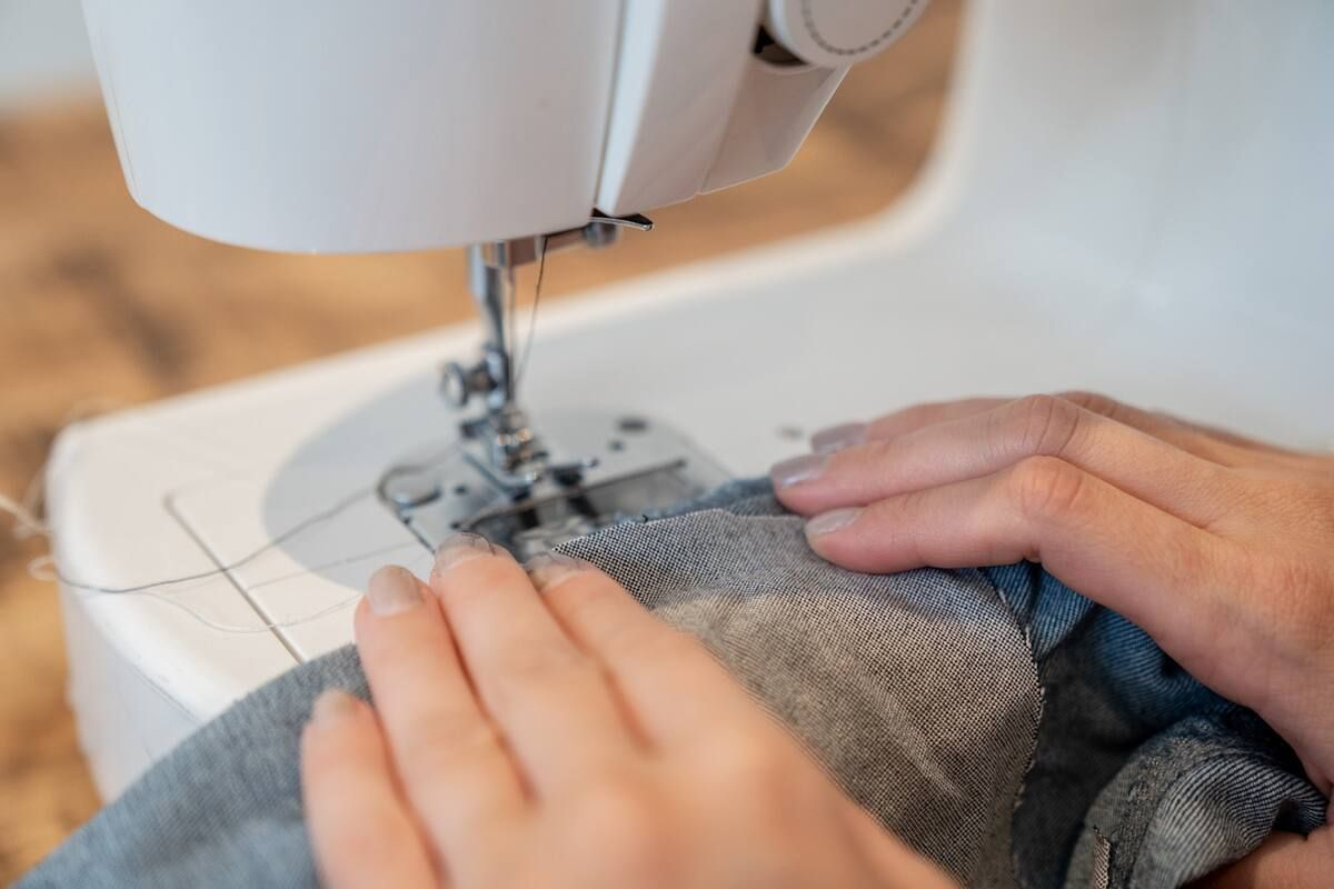 Stitching a denim patch on jeans using a sewing machine.