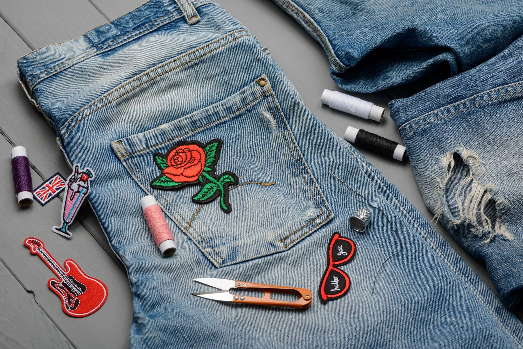 Jeans biru berbordir mawar dan peralatan jahit