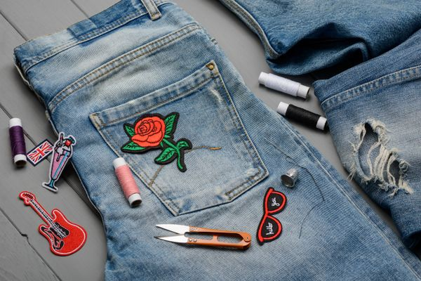 blue jeans with rose patches and a sewing kit