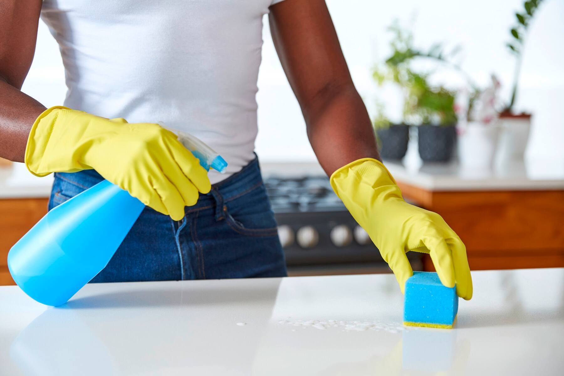 A close-up image of a female wearing yellow house gloves wiping a counter with a spray bottle