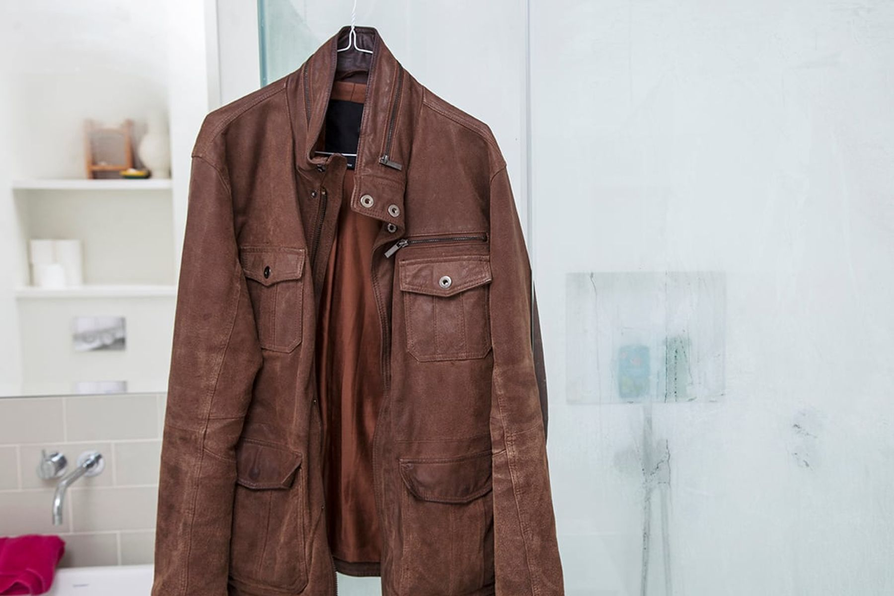 brown jacket hanging in the bathroom