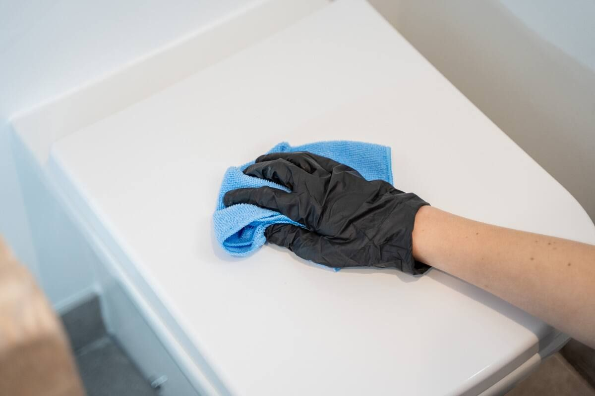 Gloved hand wiping down the lid of a toilet