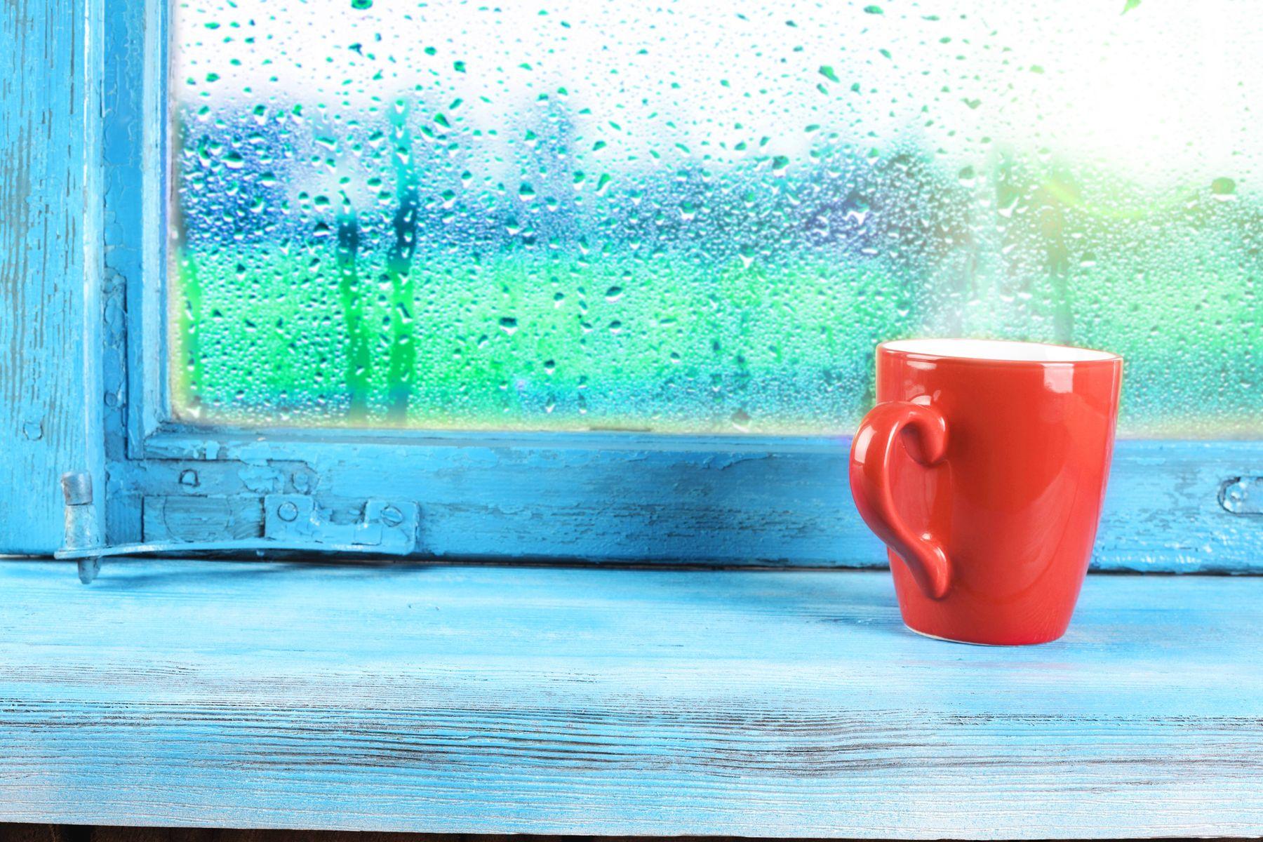 Tasse Kaffee, der an einem Fenster naß vom Regen sich lehnt