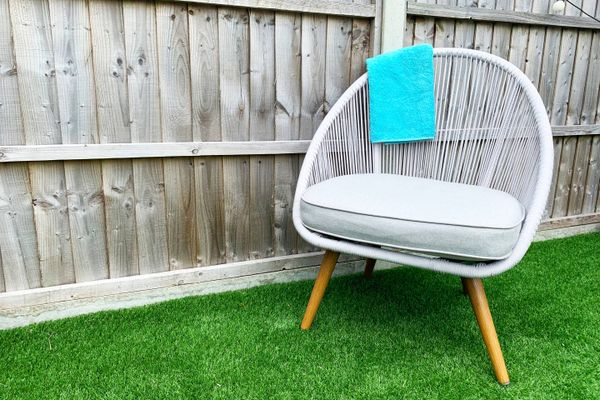 Silla de jardín sobre el pasto en un jardín pequeño