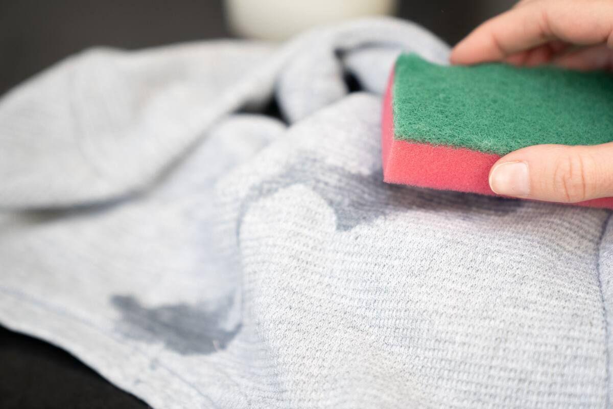 Limpiar una mancha en una prenda con una esponja