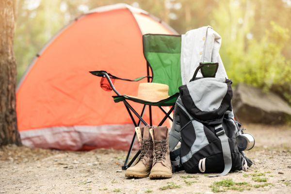 tenda, cadeira e mochila ao ar livre