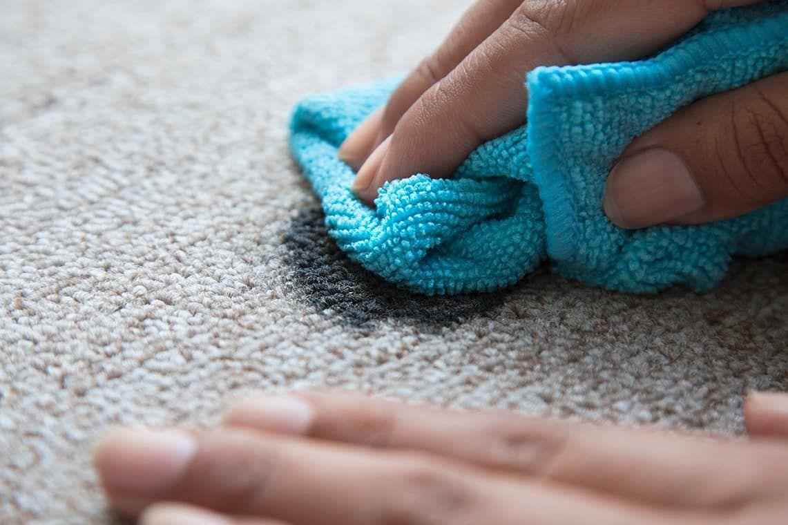 Pessoa limpando tapete com graxa com um pano azul