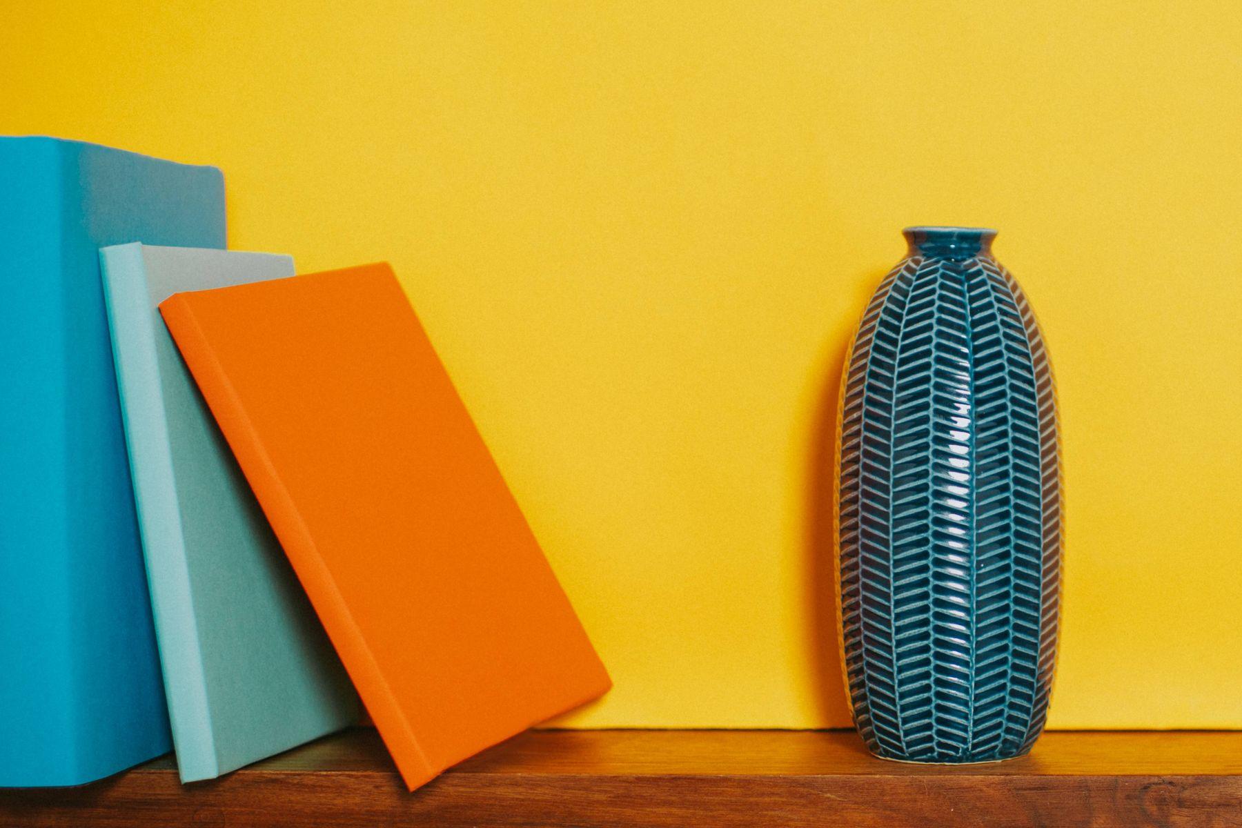 Três livros e vaso azul sobre prateleira de madeira fixada em parede amarela