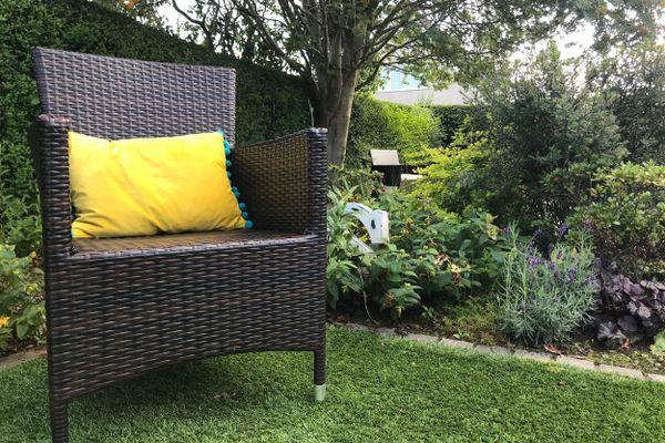 Cadeira marrom e almofada amarela em quintal cheio de plantas