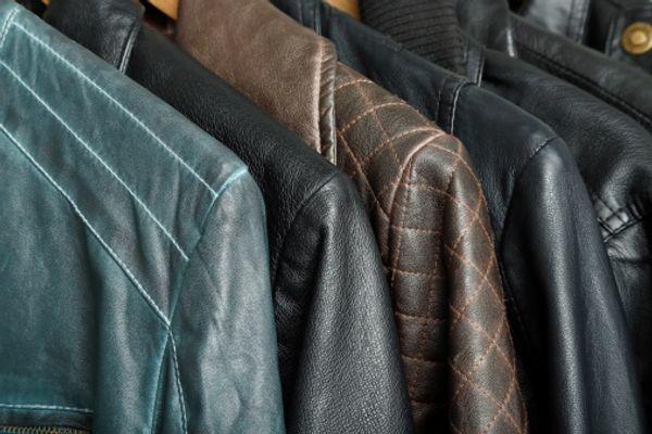 Casacos de couro diferentes em arara de roupas