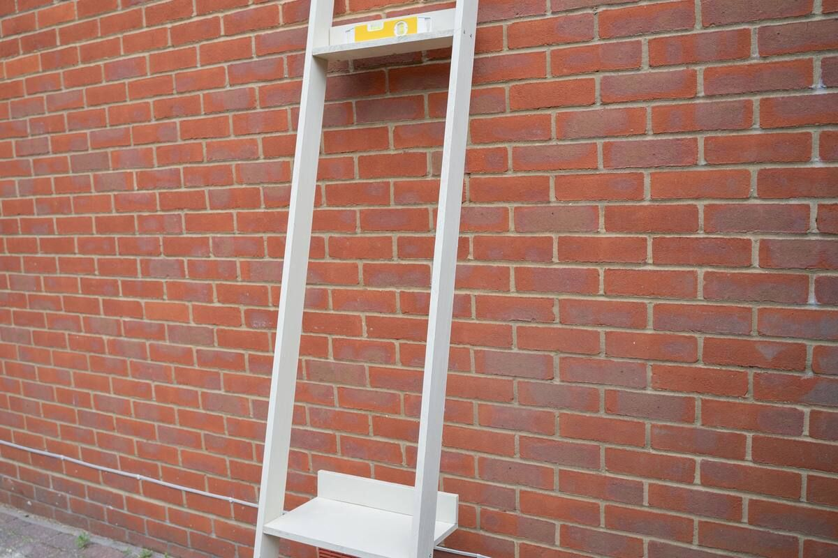 A partly assembled wooden ladder shelf propped against a wall