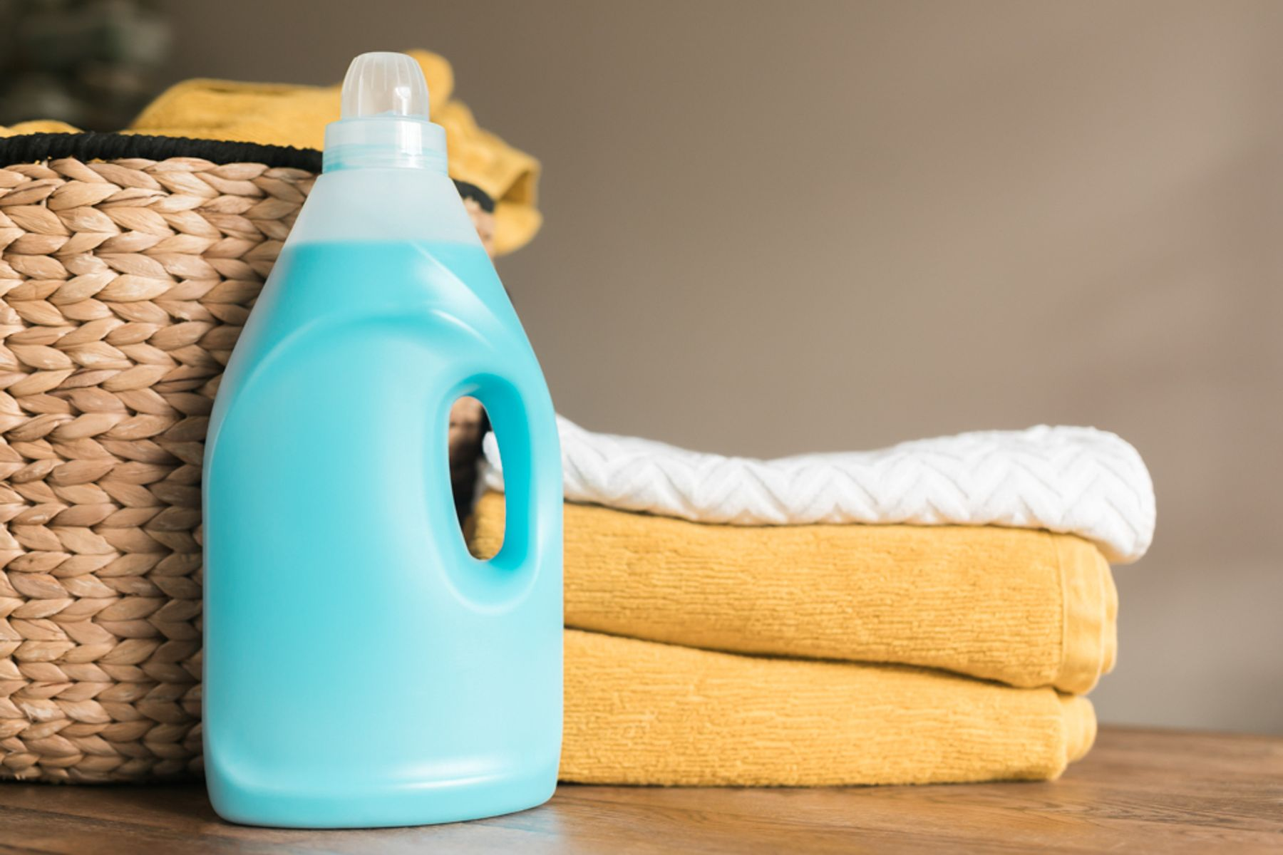 A bottle of fabric conditioner alongside folded towels and a laundry basket