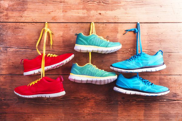 3 pairs of trainers hung up on wooden wall