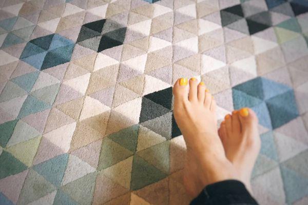 gekreuzte Beine und Füße mit gelbem Nagellack in einem karierten blauen Teppich