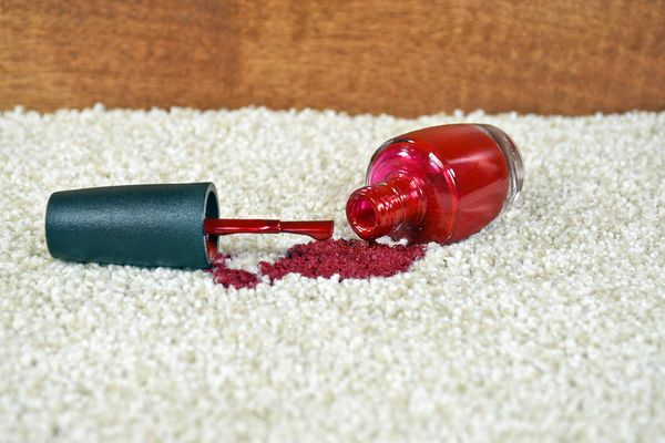 Red nail varnish bottle on a carpet with nail polish spilled on the carpet fibres