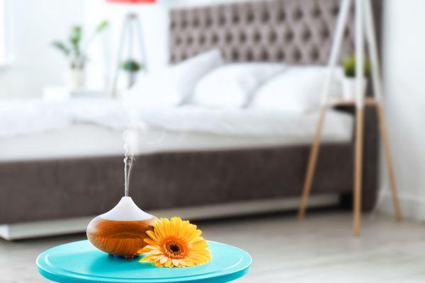 Ätherisches Öl Diffusor, Blumentopf und graues Bett mit weißen Laken