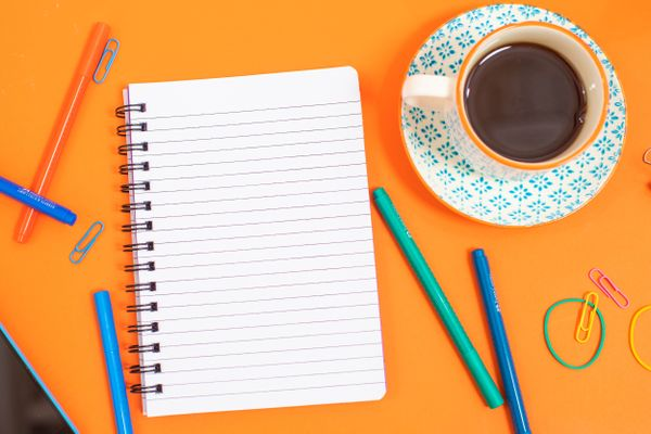 notebook for a checklist for moving house on a table with pens and a coffee