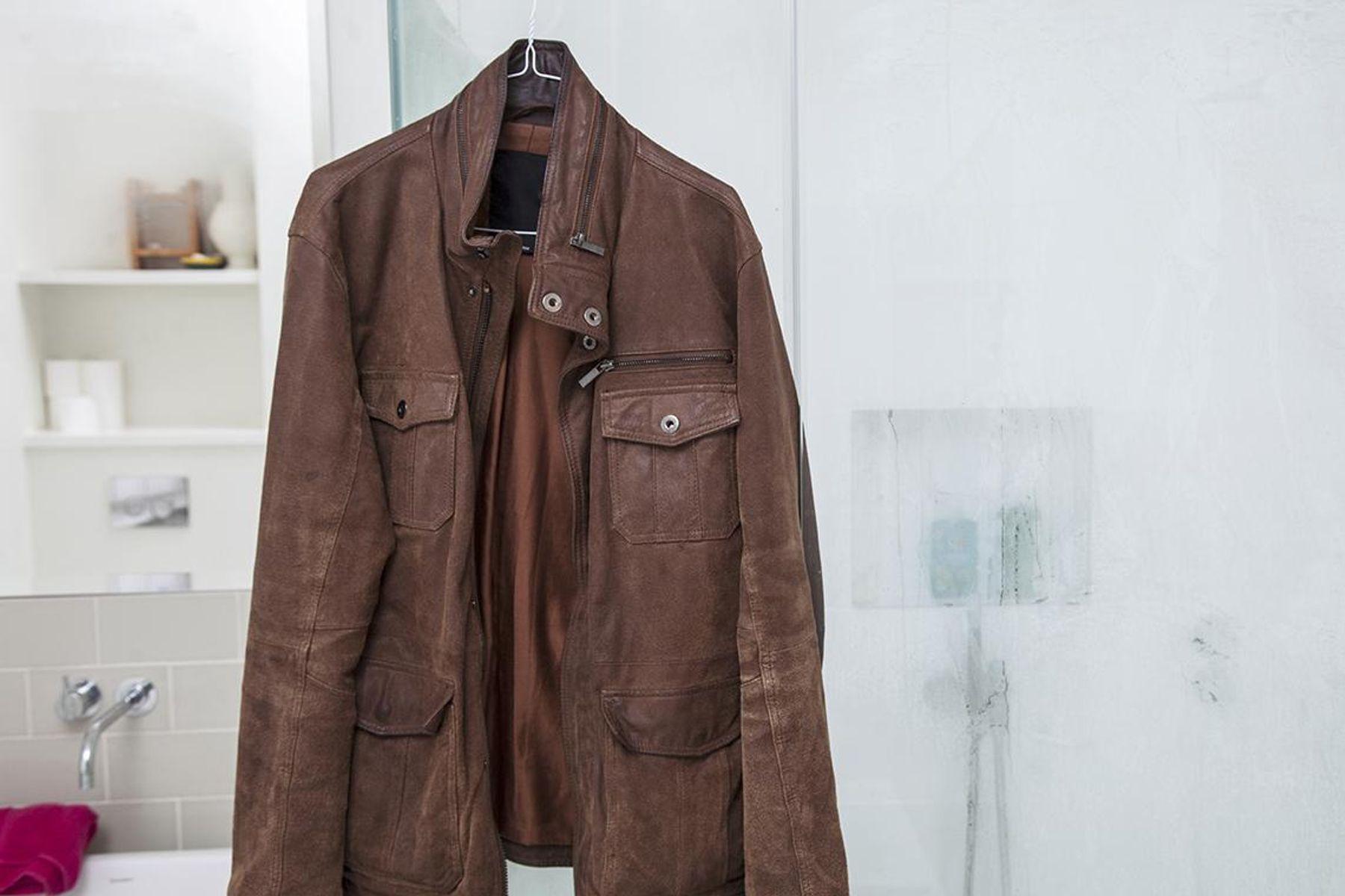Casaco de couro marrom pendurado no box do chuveiro