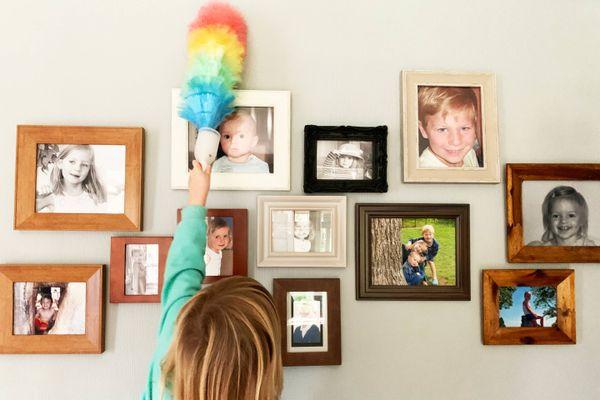 Duvarda küçük fotoğraf çerçeveleri, püskülle toz alan çocuk