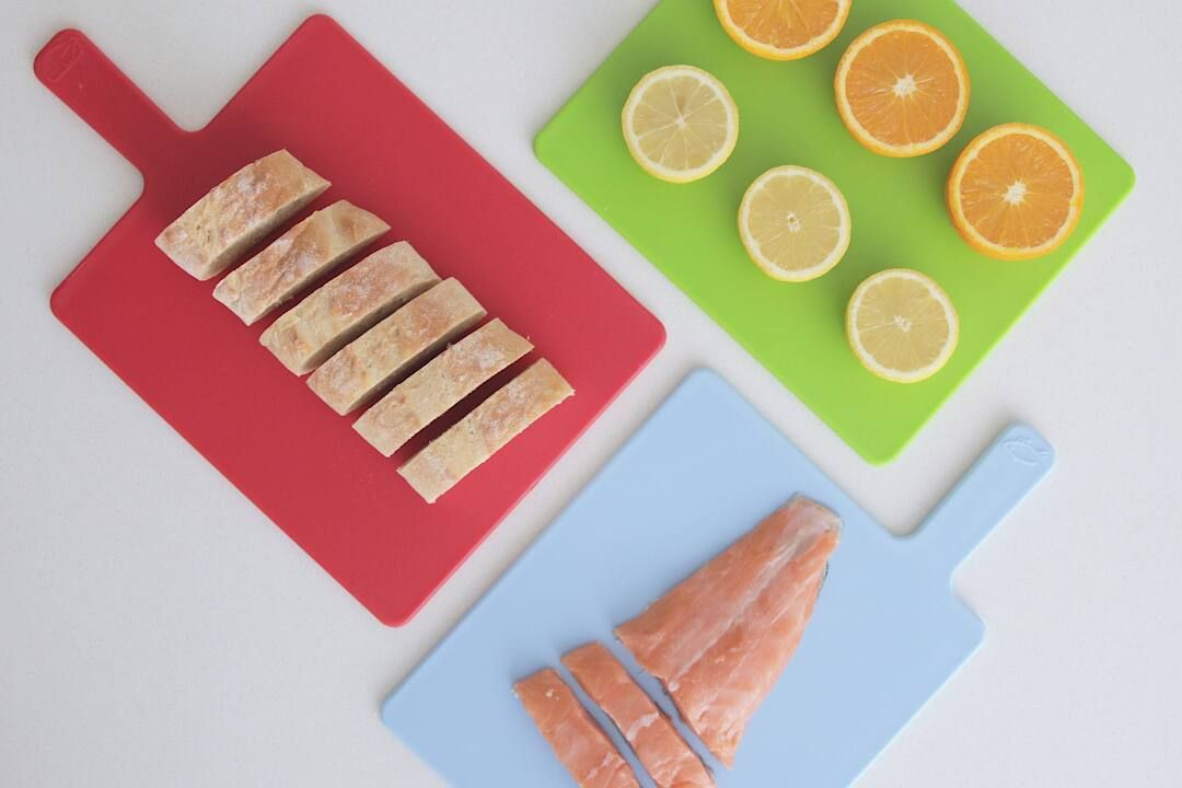 Mutfak tezgahında kesme tahtası ve dilimli balıklar ile meyveler
