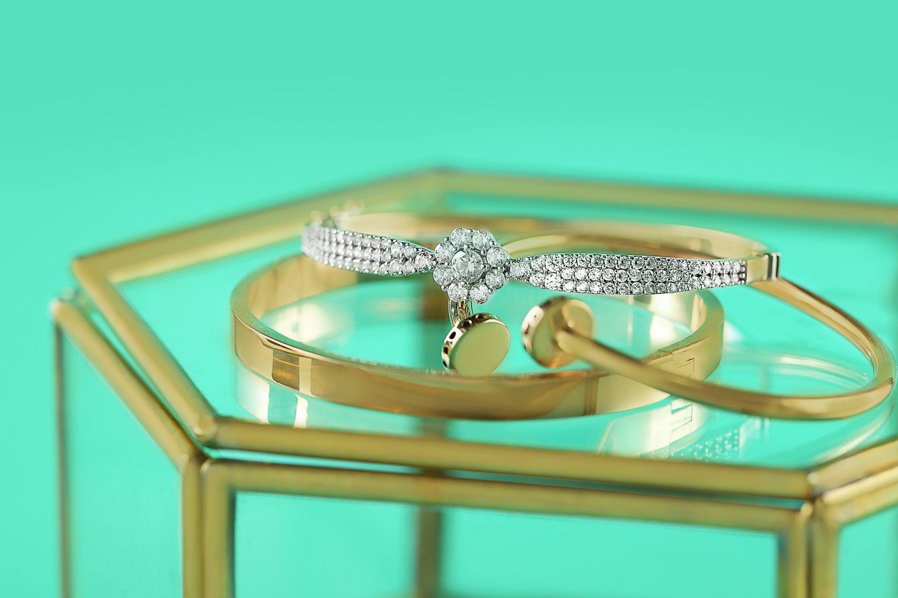 Anéis e aliança sobre porta-jóias de vidro